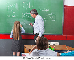 Rear of little girl solving mathematics on board with teacher looking at her