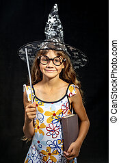 Girl sorceress, with a book and a magic wand, in a hat, on a...