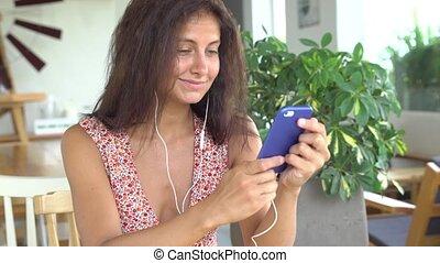 Girl speaks on her smartphone using headphones.