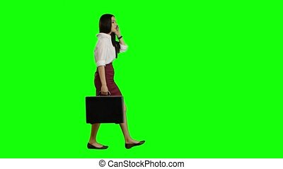 Girl speaks on the phone, in the hand holds a diplomat. Green screen