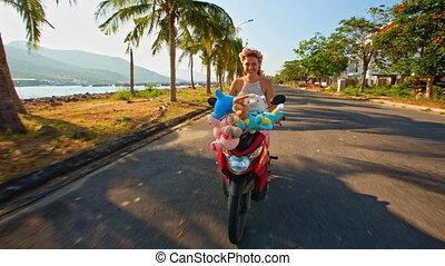 Girl Speeds on Motorbike along Oceanfront Street