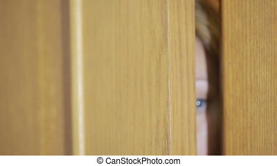 girl spies through a door crack. Eye looking through a slit
