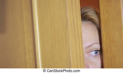 girl spies through a door crack. Eye looking through a slit