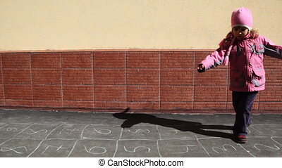 girl spinning on asphalt with picture of hopscotch games