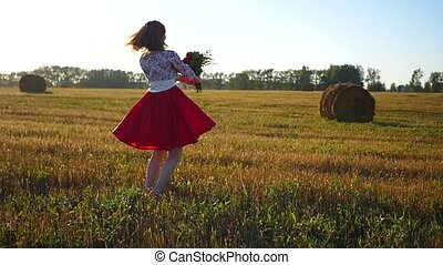 girl spinning with a bouquet of flowers at sunset