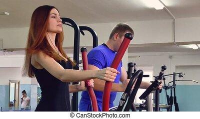 Girl sports man trainer ellipsoid on simulator involved 4? -...