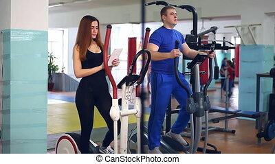 Girl sports man trainer ellipsoid on simulator involved -...