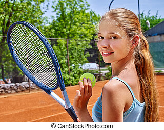 Girl sportsman with racket and ball on tennis court. Green...