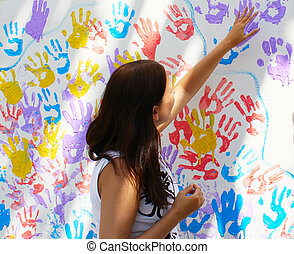 Girl stamps trace hands on wall with prints