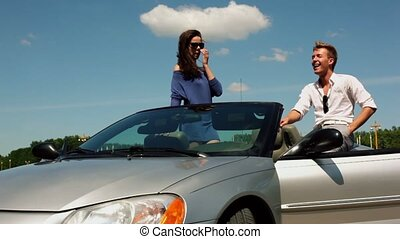 Girl stand in cabriolet with her boyfriend sit near and laugh
