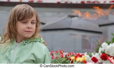 girl standing against eternal fire on monument to unknown soldier