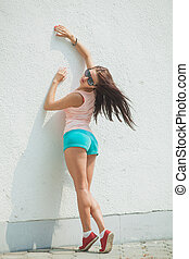 girl standing at a white wall