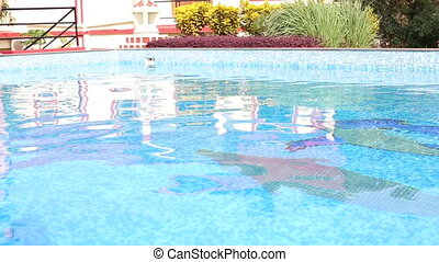 girl standing at edge of  hotel pool among planting of trees
