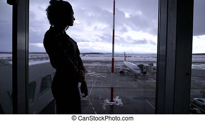Girl standing at the airport near a large window looking out on the planes that are on the runway. Silhouette of a young woman against the gray sky and standing on the territory aircraft.