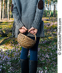 Girl standing back to camera in the forest and holding a basket.