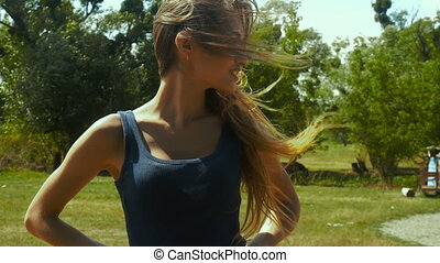 girl standing in a field and hair move against the wind