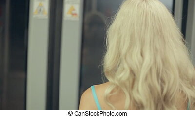 Girl standing in a subway car in front of the closed glass door