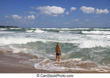 Girl standing in the sea and looks