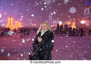 Girl standing in the square under heavy snow
