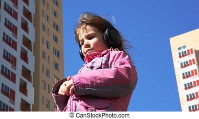 girl standing in yard with headphones