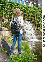 Girl standing near a waterfall in a park