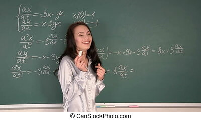Girl standing near blackboard with mathematical formulas.