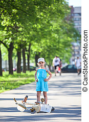 Girl standing near laying down bicycle