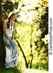girl standing next to a tree