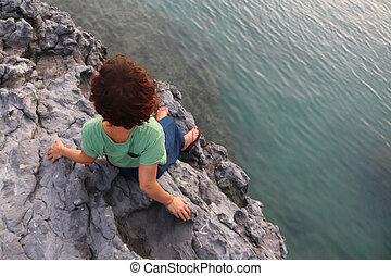 Girl standing on a rock near the sea.