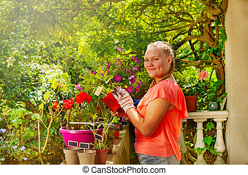 Girl standing on balcony with potted flowers