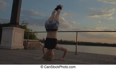 Girl standing on his head on waterfront at sunset background out of focus stock footage video
