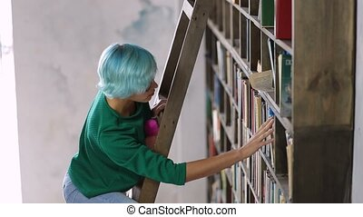 Girl standing on ladder searching book in library - Young...