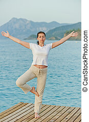 girl standing on one leg with arms outstretched to the sides