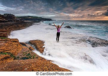 Girl standing on rocks as ocean waves wash past her feet
