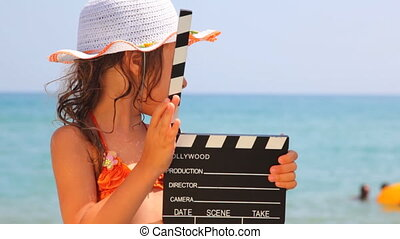 Girl standing on seashore, something tells and clicks clapboard