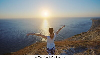 Girl standing on the cliff and raising her hands up.