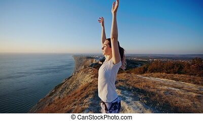 Girl standing on the cliff and raising her hands up. ?