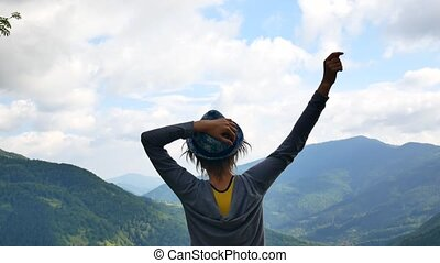 Girl standing up with arms resting at her waist while looking at the horizon on the top of a mountain Travelling up from behind her