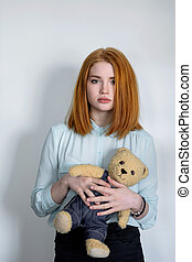 Girl standing with a teddy bear.