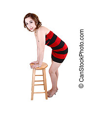 Girl standing with chair.
