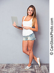 Girl standing with laptop and looking at camera
