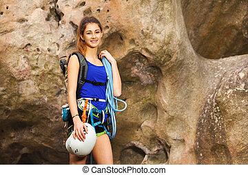 Girl standing with rock climbing equipment