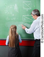 Girl Standing With Teacher Wiping Board In Classroom