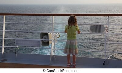 girl stands aft of cruise liner and looks at sea