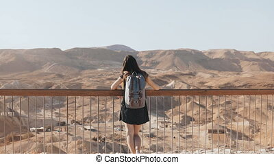 Girl stands at huge mountain view, arms wide open. Pretty European woman happy and excited. Freedom. Masada, Israel. 4K