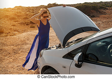 girl stands by the car with open hood