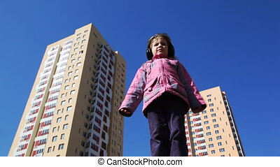 girl stands in courtyard with headphones against backdrop of...