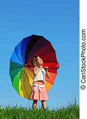 girl stands in meadow with green grass against blue sky, ...