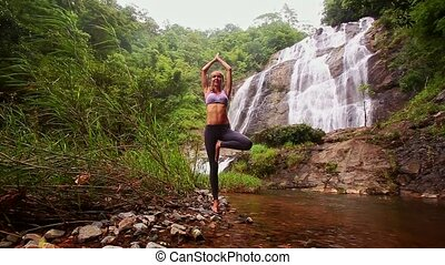 Girl Stands in Yoga Pose in Red River against Waterfall