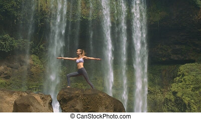 Girl Stands in Yoga Pose on Brown Rock at Waterfall